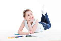 Kleines lächelndes Mädchen liegt mit dem Buch. Lizenzfreies Stockfoto