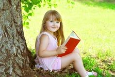 Kleines lächelndes Mädchenkind, das ein Buch auf dem Gras nahe Baum liest Lizenzfreies Stockfoto
