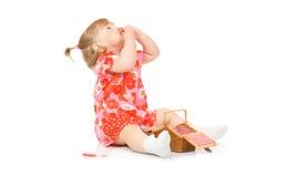 Kleines lächelndes Schätzchen im roten Kleid mit Spielzeugkorb Lizenzfreies Stockbild