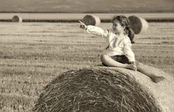 Kleines ländliches Mädchen auf dem Stroh nach Erntefeld mit Stroh bal Stockbilder