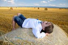 Kleines ländliches Mädchen auf dem Stroh nach Erntefeld mit Stroh bal Stockfotografie