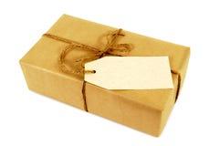 Kleines längliches Paket des braunen Papiers gebunden mit Schnur, leeres Manila-Adressen-Etikett Lizenzfreie Stockbilder