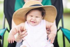 Kleines lachendes Baby, das von einem Elternteil gehalten wird Stockfotos