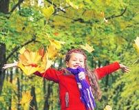 Kleines lachendes hübsches Mädchen im roten Mantel wirft gelbe Blätter im Herbstpark stockfoto