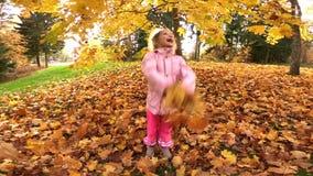 Kleines lachendes hübsches Mädchen wirft gelbe Blätter im Herbstpark stock video
