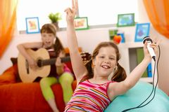 Kleines lachendes Mädchen mit Mikrofon Stockfotos