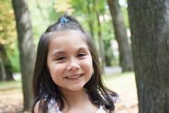 Kleines lateinisches Mädchen, das im Park lacht Lizenzfreies Stockbild
