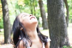 Kleines lateinisches Mädchen, das im Park lacht Stockfotografie