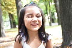 Kleines lateinisches Mädchen, das im Park lacht Lizenzfreies Stockfoto