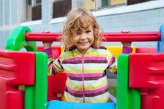 Kleines lächelndes Kind, das draußen spielt Lizenzfreie Stockbilder