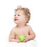 Kleines lockiges Kind, das einen grünen Apfel hält Lizenzfreies Stockfoto
