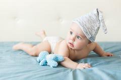 Kleines lustiges Baby mit großen blauen Augen lächelnd mit netter Kappe auf seinem Kopf lizenzfreie stockbilder