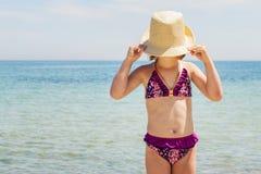 Kleines lustiges Mädchen auf dem Strand in einem Hut Lizenzfreies Stockfoto