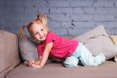 Kleines lustiges Mädchen, das auf den Sofa At Home Showing Naked-Fersen verwöhnt und spielt Er lacht, seine Zunge und Zähne zeige Stockfotografie
