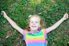 Kleines lustiges Mädchen, das auf Gras liegt Stockfoto