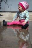Kleines lustiges Mädchen, das mit Wasser in der Pfütze spielt Stockfotos
