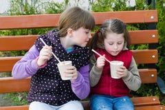 Kleines lustiges Mädchen zwei auf einer Parkbank Stockbilder