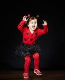 Kleines lustiges Mädchen im Marienkäferkostüm Stockbild