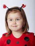 Kleines lustiges Mädchen im Marienkäferkostüm Lizenzfreies Stockfoto