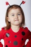 Kleines lustiges Mädchen im Marienkäferkostüm Stockfotos