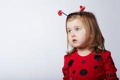 Kleines lustiges Mädchen im Marienkäferkostüm Lizenzfreies Stockbild
