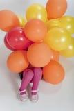 Kleines Mädchen abgedeckt in den bunten Ballonen stockfotografie