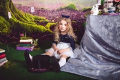 Kleines Mädchen als Alice im Märchenland, das auf dem Boden sitzt stockfotos