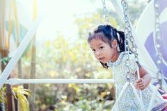 Kleines Mädchen Asiens spielt Schwingen am Hinterhof am sonnigen Tag Stockbild