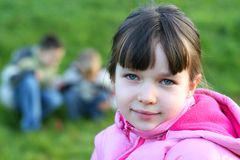 Kleines Mädchen auf dem Gebiet mit Spielkameraden Stockbilder
