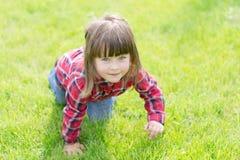 Kleines Mädchen auf dem Gras lizenzfreie stockbilder