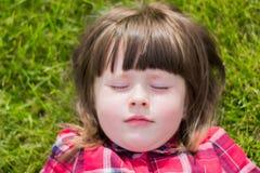 Kleines Mädchen auf dem Gras lizenzfreies stockbild