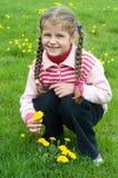 Kleines Mädchen auf dem Löwenzahngebiet lizenzfreies stockfoto