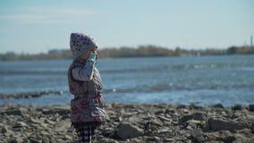 Kleines Mädchen auf dem Steinstrand nahe dem Fluss stock footage