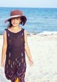 Kleines Mädchen auf dem Strand, der lustigen Hut trägt. Stockfotografie