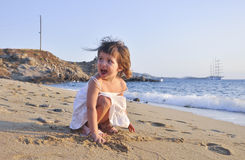 Kleines Mädchen auf dem Strand in einem weißen Kleid Stockbilder