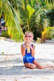 Kleines Mädchen auf dem Strand exotisches Cocktail, Meer, Ozean, Bikini, Sommer, tropisch schauende draußen trinkend Kamera Lizenzfreies Stockbild