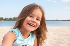 Kleines Mädchen auf dem Strand, langes Haar, Lachen, glücklich, Porträt, Kind, Ufer, Sand Stockfotografie