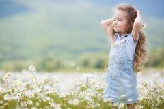 Kleines Mädchen auf dem weißen Kamillengebiet Lizenzfreies Stockfoto