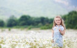 Kleines Mädchen auf dem weißen Kamillengebiet Lizenzfreie Stockfotos