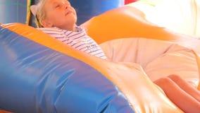 Kleines Mädchen auf einem aufblasbaren Sommerspielplatz stock footage