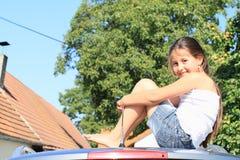 Kleines Mädchen auf einem Auto stockbilder