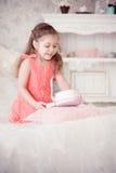 Kleines Mädchen auf einem Bett mit rosa Kasten Stockbilder