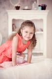 Kleines Mädchen auf einem Bett mit rosa Kasten Stockfotos
