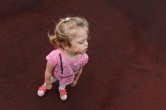 Kleines Mädchen auf einem dunkelroten Hintergrund Stockfotografie