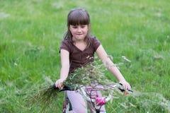 Kleines Mädchen auf einem Fahrrad in der Natur lizenzfreie stockfotos