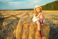 Kleines Mädchen auf einem Gebiet mit Heu rollt lizenzfreie stockfotos