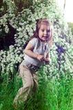 Kleines Mädchen auf einem Hintergrund ein Busch mit Blumen Lizenzfreie Stockfotos