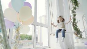 Kleines Mädchen auf einem Schwingen im Studio Schwingkind stock video