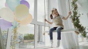 Kleines Mädchen auf einem Schwingen im Studio Schwingkind stock footage