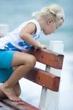Kleines Mädchen auf einer Bank   Lizenzfreie Stockfotografie